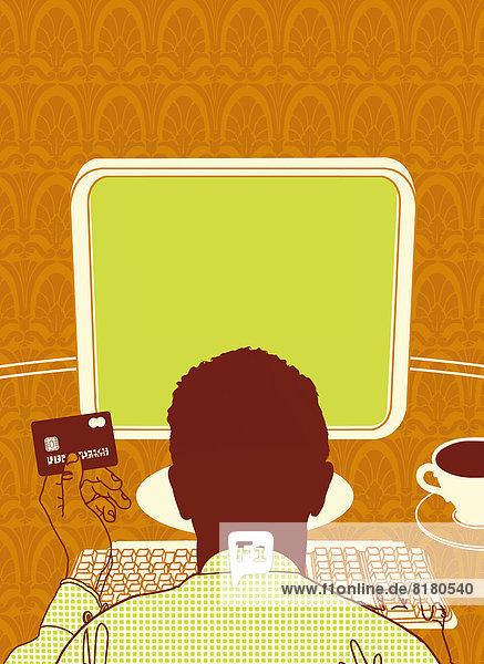 Mann mit Kreditkarte am Computer