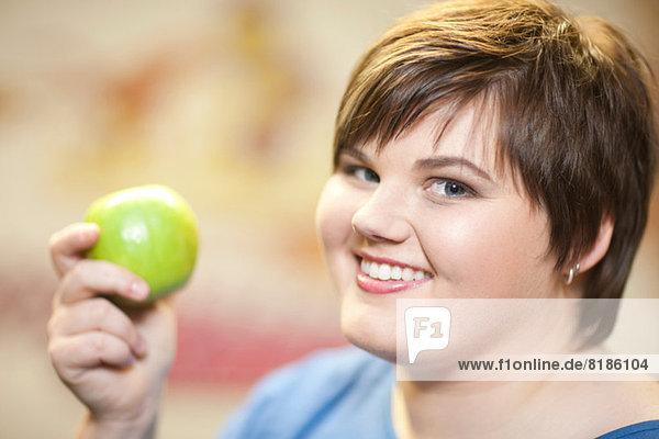 Nahaufnahme des Porträts einer jungen Frau mit einem Apfel