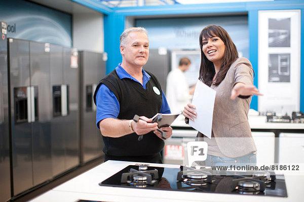 Frau und Küchengeräteverkäufer im Showroom