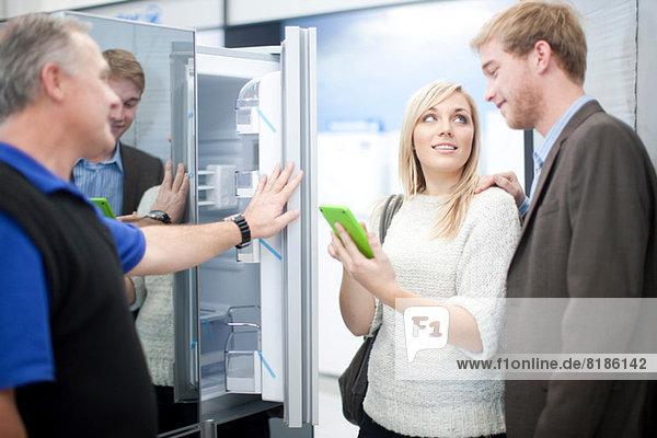 Junges Paar beim Blick auf den Kühlschrank im Showroom