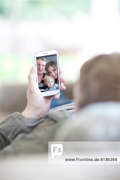 Mann betrachtet Familienfoto auf dem Handy