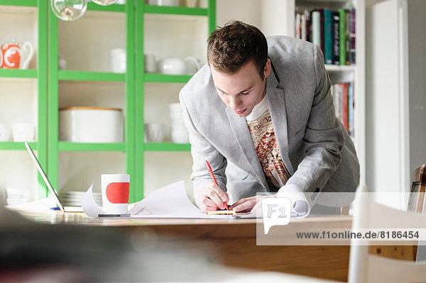 Mann beugt sich über Arbeitsunterlagen