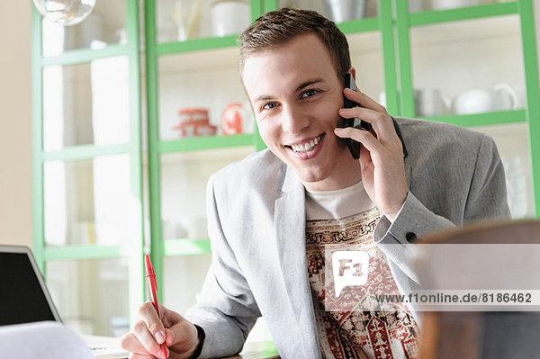 Mann lächelt und hört dem Handy zu