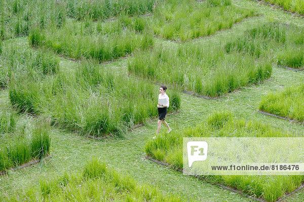 Junge Büroangestellte beim Spaziergang durch das Graslabyrinth