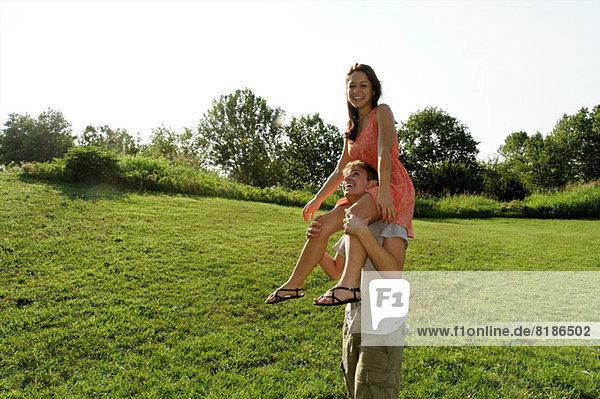 Junge Frau auf den Schultern junger Männer sitzend