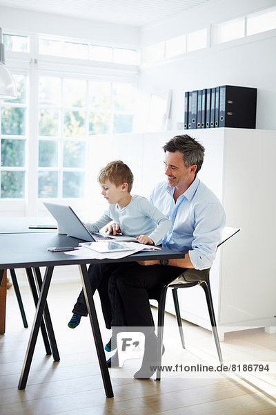 Man sitting at desk with son on his knee with laptop computer and paperwork
