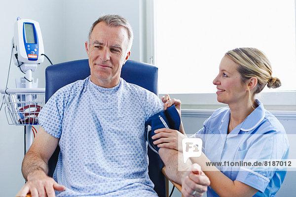 Krankenschwester  die den Blutdruck des Patienten nimmt