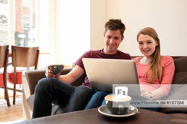 Junges Paar beim Betrachten des Personalcomputers im Café