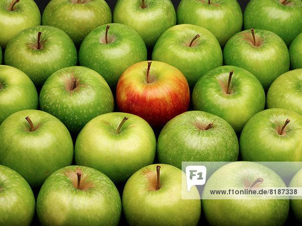 Gruppe grüner Äpfel mit einem roten Apfel