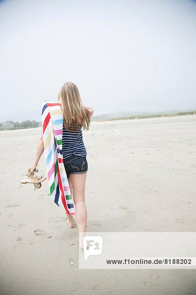 Junge Frau geht mit Handtuch am Strand spazieren