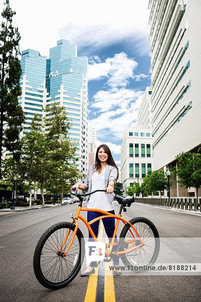 Junge Frau stehend mit Fahrrad in der Stadt  lächelnd
