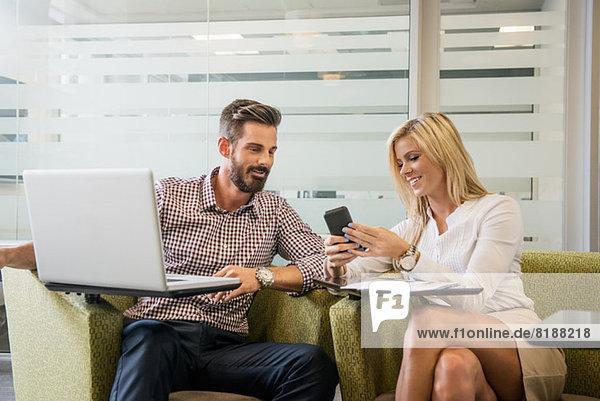Junge Geschäftskollegen  die beim Meeting auf das Smartphone schauen