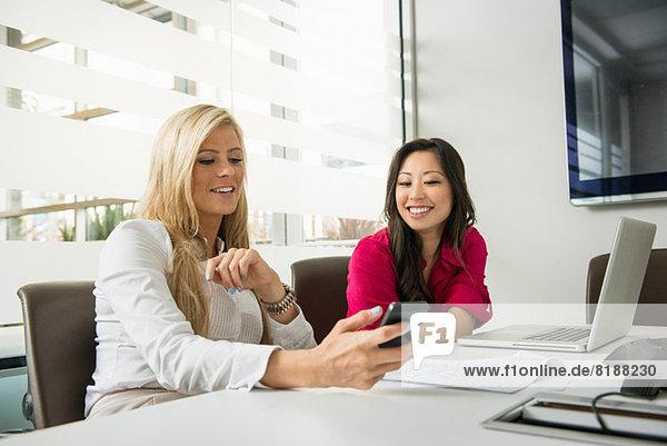 Junge Geschäftsfrauen bei der Suche nach einem Smartphone im Konferenzraum
