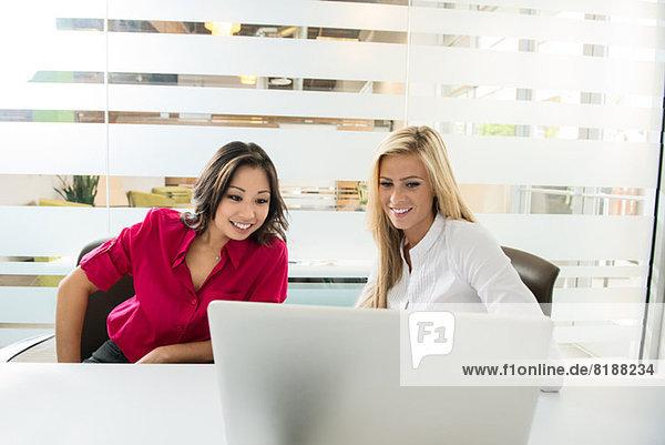 Junge Geschäftskollegen beim Blick auf den Laptop im Konferenzraum