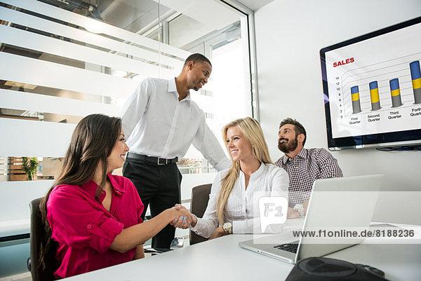 Junge Geschäftskollegen beim Händeschütteln im Konferenzraum