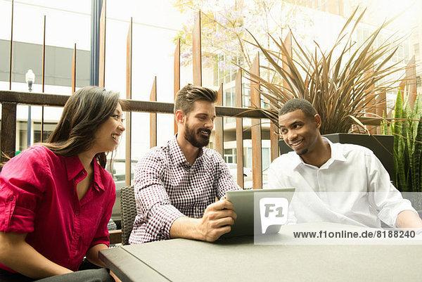 Junge Geschäftskollegen  die sich beim Meeting mit dem digitalen Tablett beschäftigen