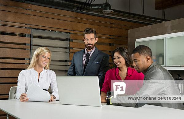 Junge Geschäftskollegen suchen Laptop in der Sitzung