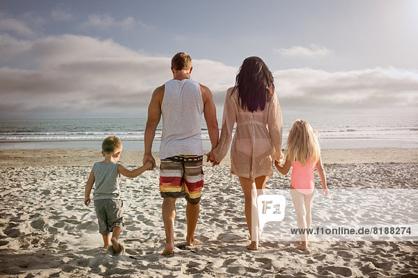 Young family holding hands together on beach  rear view
