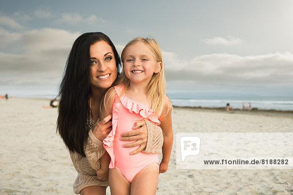 Junge Frau lächelt mit Tochter am Strand  Portrait