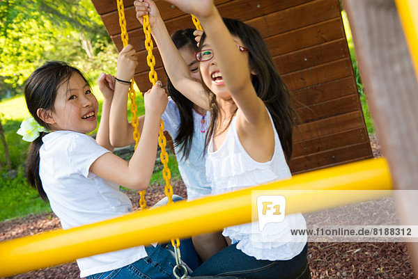 Three girls playing on swing