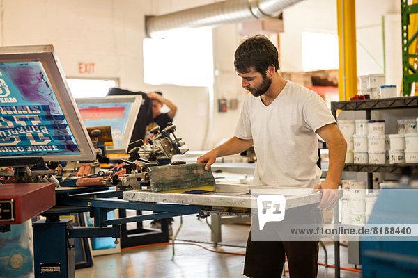 Arbeiter  der in der Siebdruckwerkstatt Farbe auf den Rahmen drückt.
