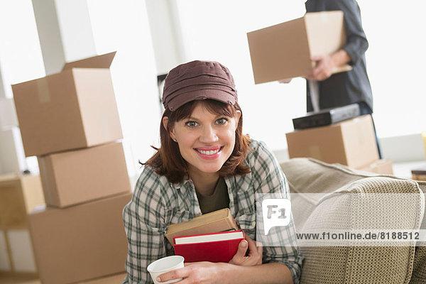 Frau sitzend mit Büchern beim Umzug nach Hause