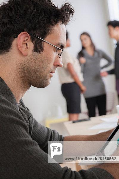 Männlicher Büroangestellter mit digitalem Tablett