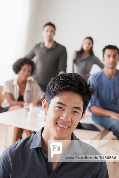 Porträt eines jungen Büromenschen vor Kollegen