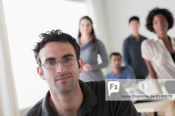 Porträt eines männlichen Büroangestellten vor Kollegen