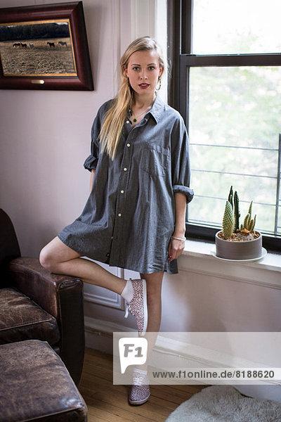 Junge Frau auf einem Bein im Zimmer stehend  Portrait