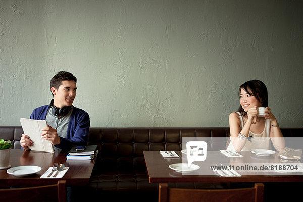 Junger Mann und junge Frau lächeln sich im Restaurant an.