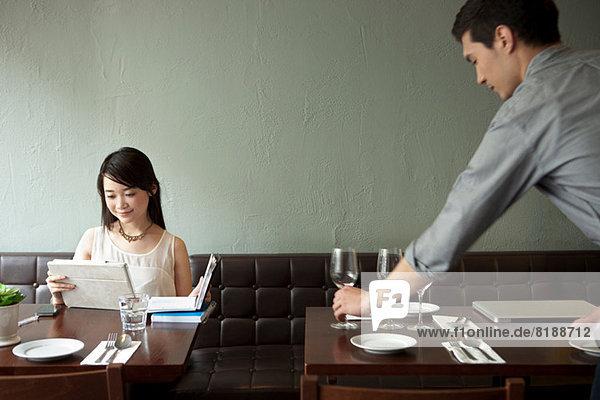 Junge Frau mit digitalem Tablett im Restaurant  Kellnertisch