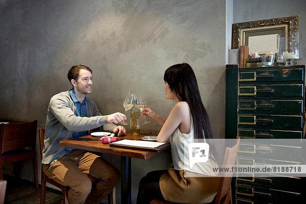 Junges Paar toastet Weißwein im Restaurant