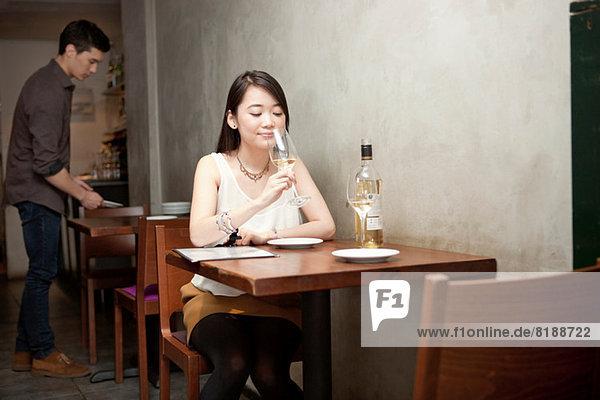 Junge Frau mit Weinglas im Restaurant