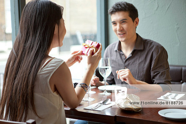 Young couple in restaurant  woman holding gift box