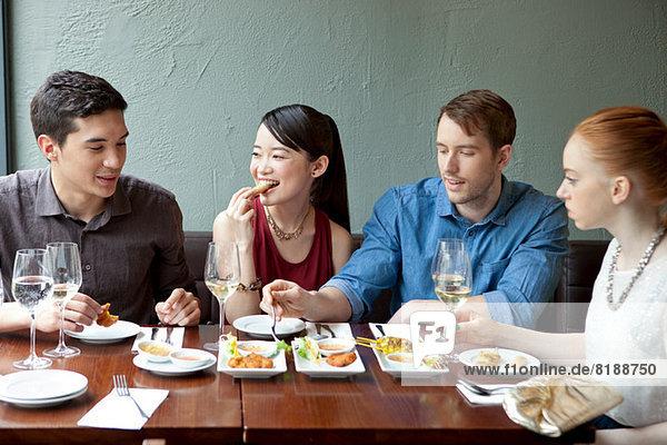 Vier Freunde beim Essen im Restaurant