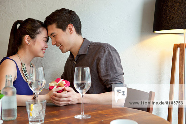 Young couple in restaurant with gift