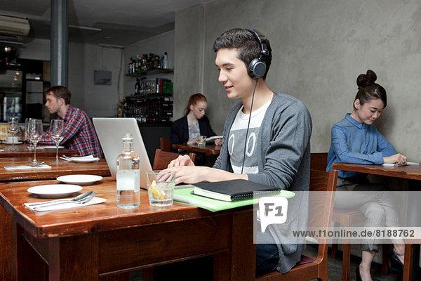 Junger Mann mit Kopfhörer und Laptop im Cafe