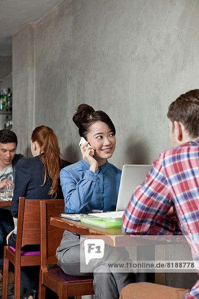 Student am Handy im Cafe mit Laptop