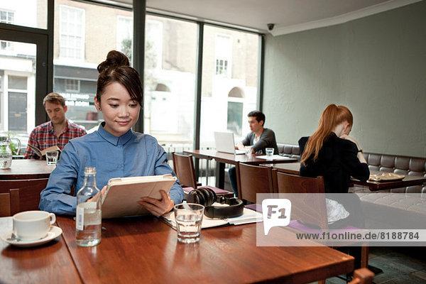 Junge Frau mit digitalem Tablett im Cafe