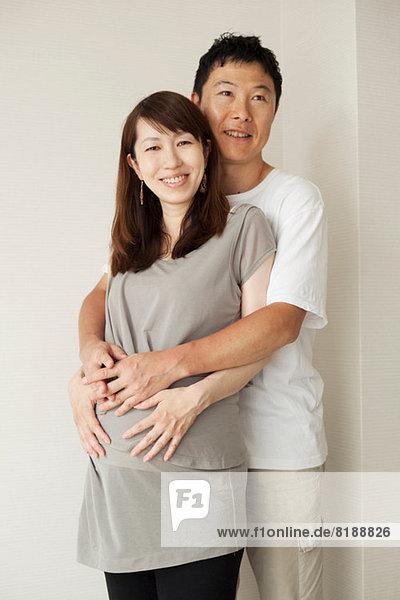Mann umarmt schwangere Frau  Portrait