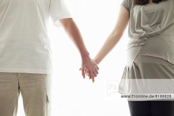 Schwangere Frau und Mann halten sich an den Händen  Porträt