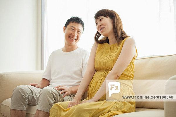 Mann und schwangere Frau auf dem Sofa sitzend