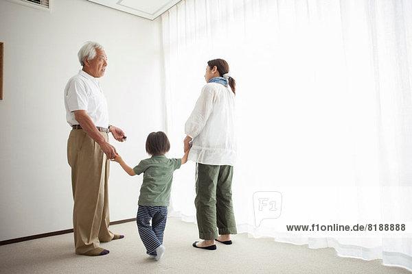 Drei Generationen Familie stehen am Fenster und halten sich an den Händen.