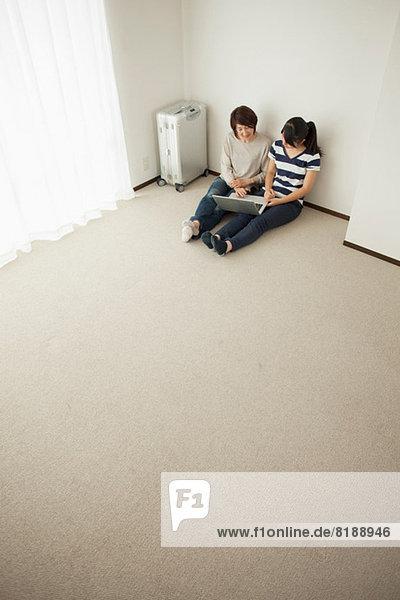 Mutter und jugendliche Tochter auf dem Boden sitzend mit Laptop