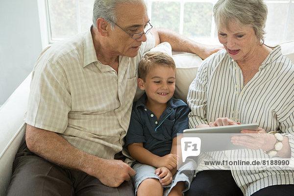 Großeltern zeigen Jungen digitales Tablett auf Sofa