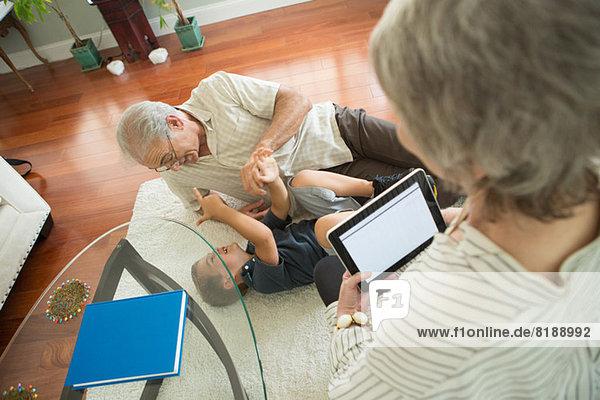 Senior Mann kitzelt Enkel auf dem Teppich