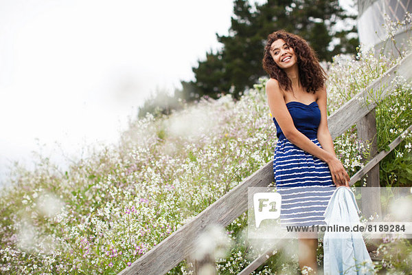 Young woman laughing by meadow