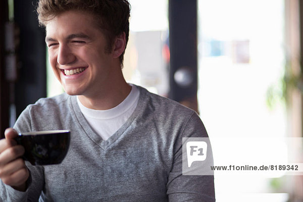 Portrait of young man in cafe holding cup