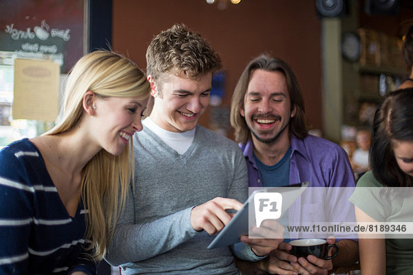 Group of people gathered around digital tablet in cafe